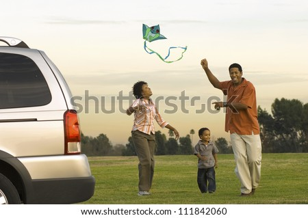Family flying kite together in the park