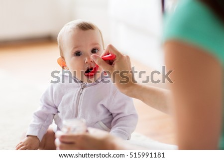family, food, child, eating and parenthood concept - mother with puree and spoon feeding little baby at home #515991181