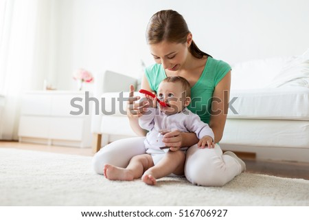 Shutterstock family, food, child, eating and parenthood concept - mother with puree and spoon feeding little baby at home