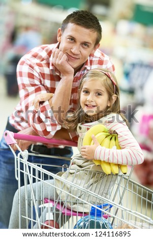 Family food shopping Young man father and little girl daughter on trolley cart in supermarket