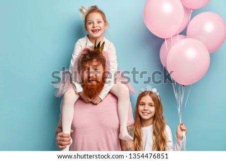 Family, friendly relationships, fatherhood and celebration concept. Tired red haired father gives piggyback to small daughter, celebrates birthday party with children, enjoy happy moments together. #1354476851