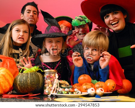 Family/friends posing for the camera in their halloween costumes. They are standing in the kitchen with party food and treats set out in front of them.