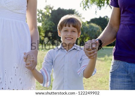 Family fun, happy mother, father and son holding hands in park and looking at camera. Waist up, front view
