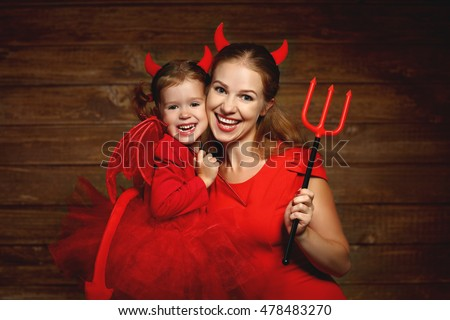 Family fun mother and child daughter having fun and celebrate Halloween in devil costume