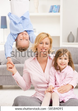Family fun. Mother holding her daughter on knees, boy hangging upside down.