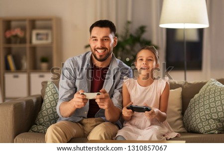 family, gaming and entertainment concept - happy father and little daughter with gamepads playing video game at home