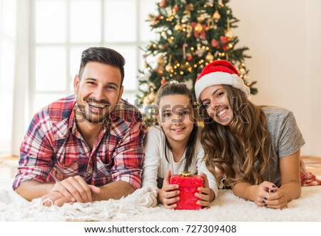 Family gather around a Christmas tree, holding a  present