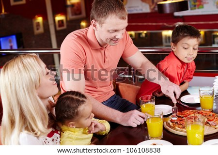 Family gathered together to enjoy pizza at the local pizzeria