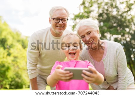 family, generation and people concept - happy smiling grandmother, grandfather and little granddaughter taking selfie by smartphone at park