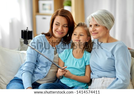 family, generation and technology concept - happy mother, daughter and grandmother taking picture by smartphone on selfie stick at home
