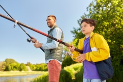 family, generation, summer holidays and people concept - father and son with fishing rods on river berth