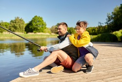family, generation, summer holidays and people concept - happy smiling father and son with fishing rods on river berth