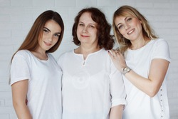 Family, grandmother, grandson, dad, mother in blue jeans and white T-shirts in casual style in a photo studio