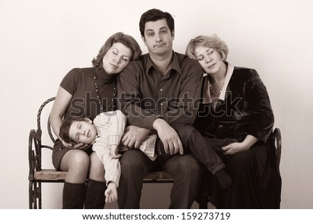 Family - Grandmother, mother, father and child sitting on the bench and sleeping Black and white portrait