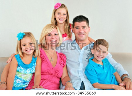 Family Group of Five Portrait Sitting on Sofa Indoor