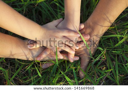 family hand stack together on the grass