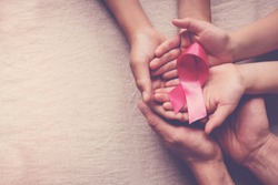 Family hands holding pink ribbon, breast cancer awareness, October pink concept, world cancer day