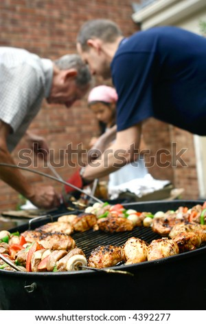 Family having a barbecue in the garden, helping each other out with the food preparation.