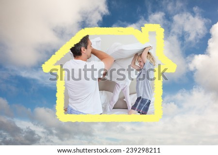 Family having a pillow fight against blue sky with white clouds