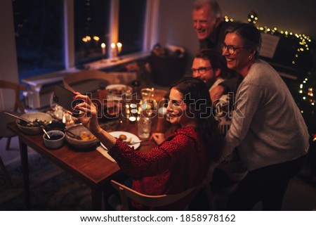 Family having a Thanksgiving dinner and having video chat with their loved one. Family having a video call during Christmas dinner.