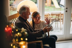Family having a video call on table pc during christmas. Senior couple greeting family during a video call on a Christmas eve.