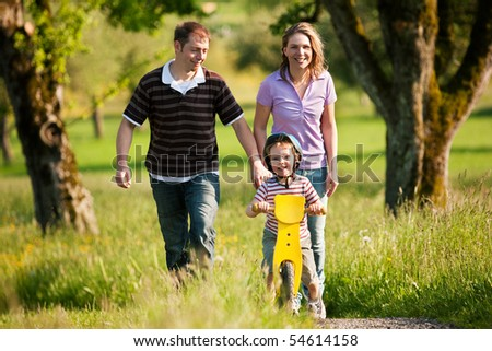 Family having a walk outdoors in summer, their little son using a training bike, unspoiled nature