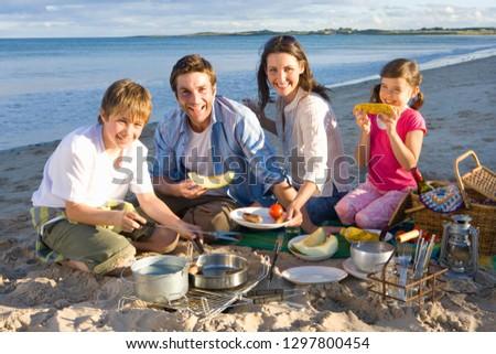 Family having barbecue picnic on sandy beach at camera