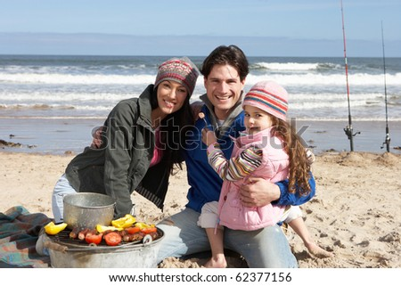 Family Having Barbeque On Winter Beach - stock photo
