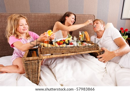 family having breakfast in bed - feeding each other