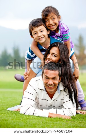 Family having fun lying on top of each other outdoors