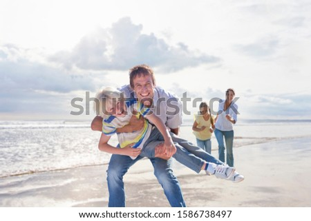 Family Having Fun On Beach Vacation Together