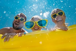 Family having fun on summer vacation. People jumping in swimming pool. Active lifestyle concept. Spring break!