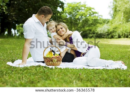 Family having fun on the picnic in the meadow.
