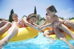 Family having fun riding inflatable ring at the pool