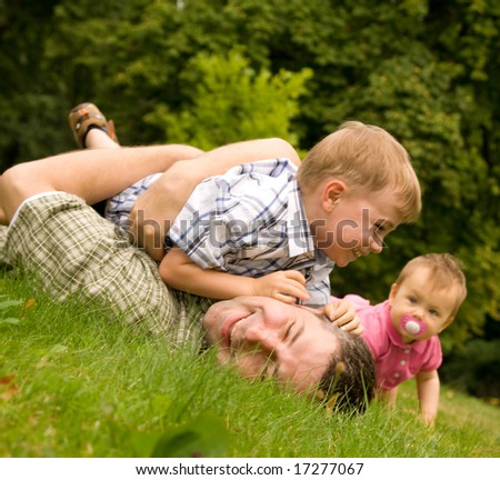 Family having fun together on grass, rural background. Father wrestling with young son as baby sister watches.