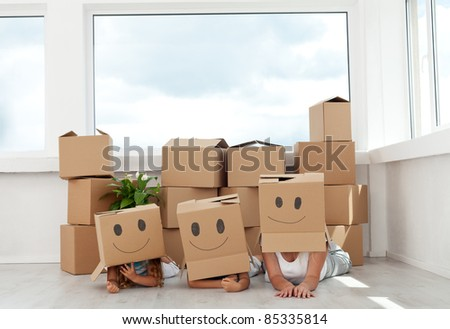 Family having fun with cardboard boxes moving into their new home