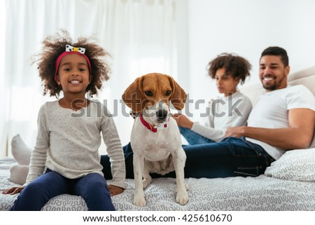 Family having fun with his pet in a bed.