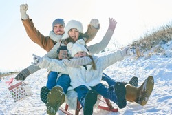 Family having fun with sled driving and laughing with joy