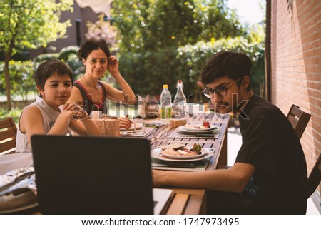 Family having lunch outdoors in their home garden while watching a movie with laptop. Real lifestyle. stock photo