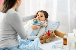 family, health and people concept - mother giving mug with hot tea to sick little daughter lying in bed at home