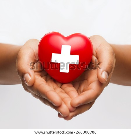 family health, charity and medicine concept - african american female hands holding red heart with cross sign
