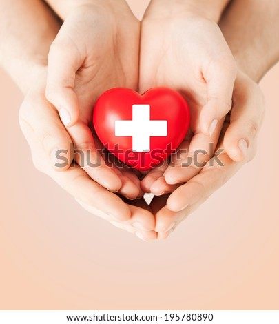 family health, charity and medicine concept - male and female hands holding red heart with cross sign #195780890
