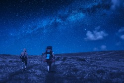 Family hikers have a trekking in a mountains under the starry sky at night. Far from people.
