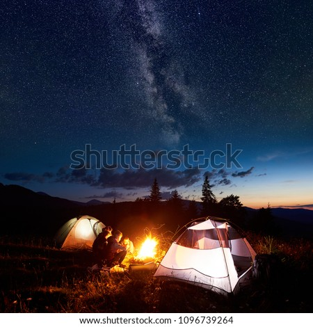 Family hikers mother, father, two sons having a rest at night camping in mountains, sitting on log beside campfire and two illuminated tents, under amazing view of evening sky full of stars, Milky way #1096739264