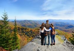 Family hiking in autumn mountains enjoying beautiful mountain view. People on hiking trip in Blue Ridge Mountains. North Carolina, USA.