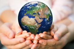 Family holding Earth in hands. Elements of this image furnished by NASA