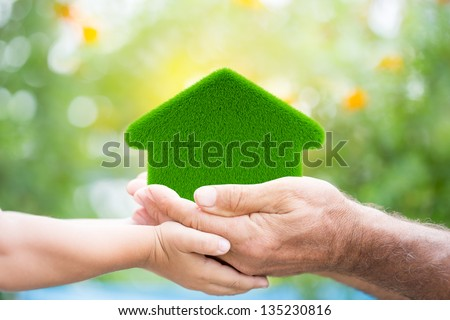 Family holding grass house in hands against green spring background. Environment protection concept