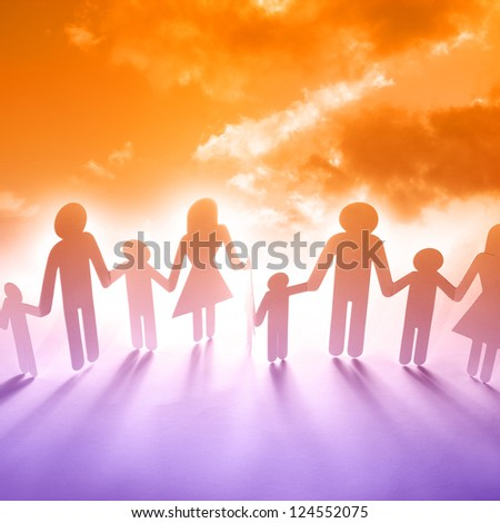 Family holding hands in front of sunset
