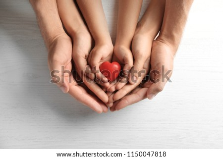 Family holding small red heart in hands on wooden background #1150047818