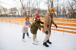 Family holding to each other while skating on the rink in the park